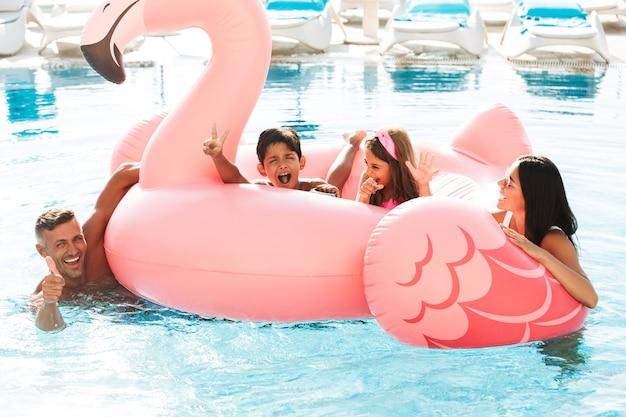 Foto de família feliz com crianças nadando na piscina com anel de borracha rosa, fora do hotel durante as férias