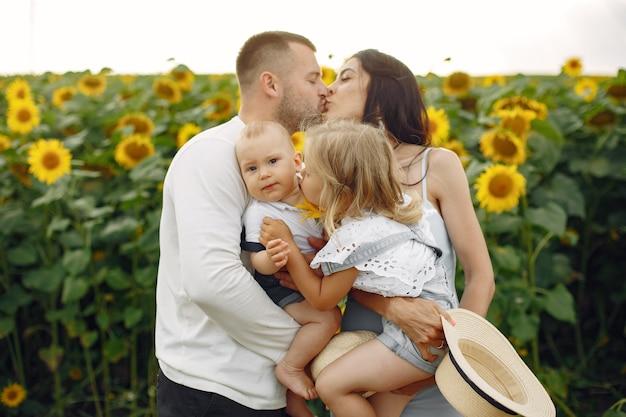 Foto de família feliz. pais e filha. família unida no campo de girassol. homem de camisa branca.