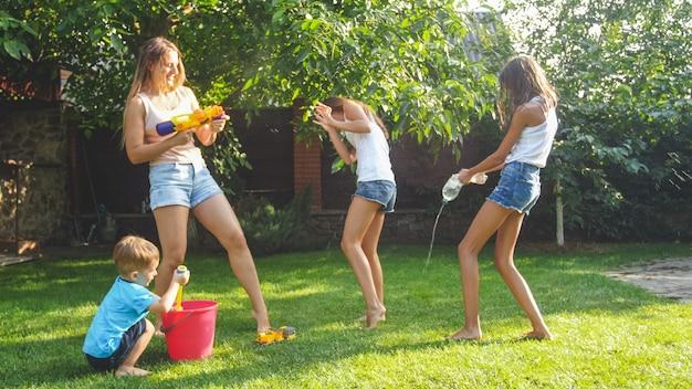 Foto de família feliz rindo espirrando água com pistolas de água e uma mangueira de jardim no quintal. pessoas brincando e se divertindo em um dia quente e ensolarado de verão