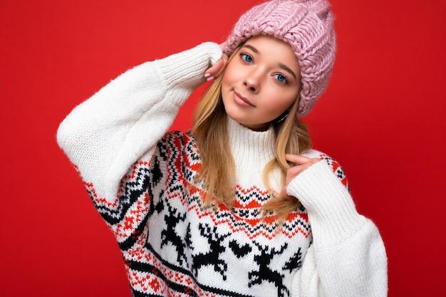 Foto de fascinante jovem loira encantadora isolada sobre a parede de fundo vermelho, vestindo uma camisola de inverno e chapéu rosa, olhando para a câmera.