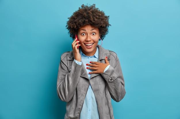 Foto de feliz adolescente de cabelos encaracolados surpresa. expressão alegre fala via celular reage de forma surpreendente em notícia incrível usa jaqueta cinza