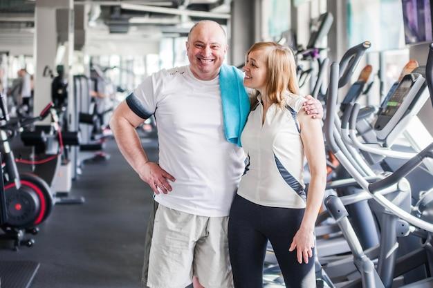 Foto de feliz casal mais velho no ginásio. abraços e olham para a câmera