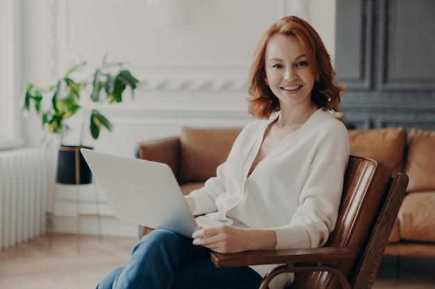 Foto de feliz freelancer europeu mulher satisfeito com trabalho remoto, trabalha freelance no computador portátil