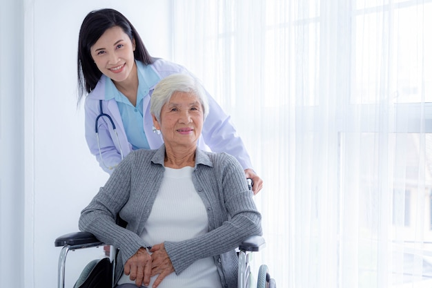 Foto de feliz médica e pacientes idosos em cadeira de rodas. cuidado do paciente idoso e cuidados de saúde, conceito médico.