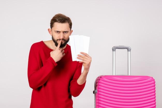 Foto de férias de turista jovem com bolsa rosa segurando bilhetes na parede branca.