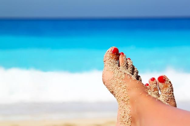 Foto de foco raso de pés femininos arenosos com pedicure vermelha na praia