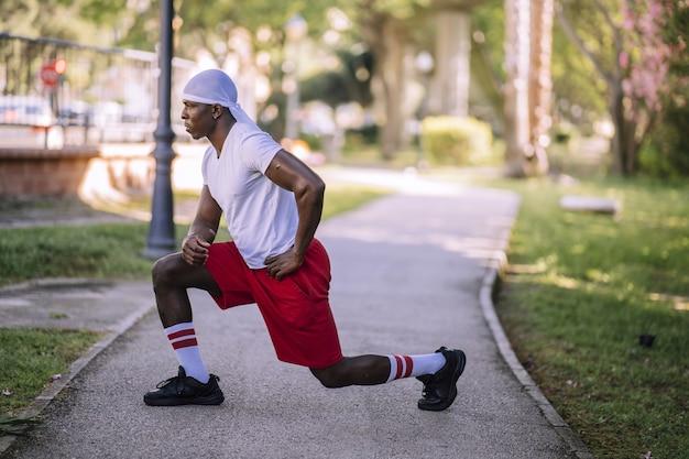 Foto de foco raso de um homem afro-americano com uma camisa branca se espreguiçando no parque