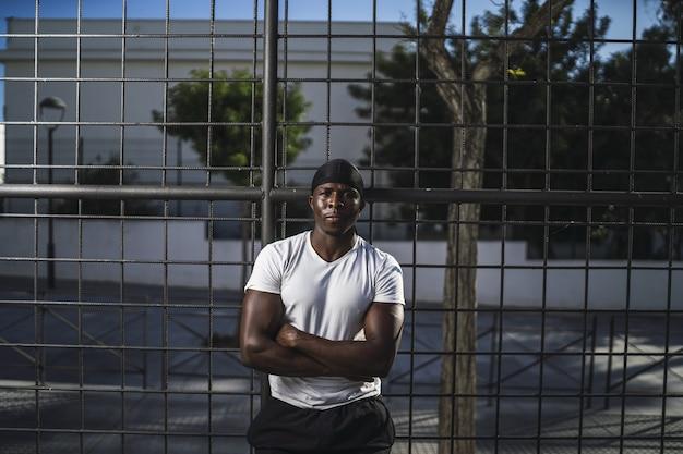 Foto de foco raso de um homem afro-americano em uma camisa branca encostado em uma cerca com os braços cruzados