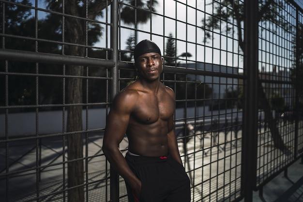 Foto de foco raso de um homem afro-americano seminu encostado na cerca