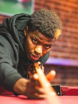 Foto de foco raso de um jovem negro em uma sala de jogos de bilhar