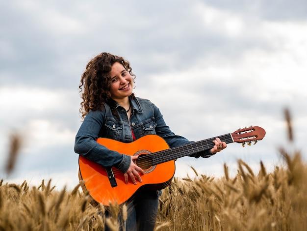 Foto de foco raso de uma bela jovem tocando violão em um campo de trigo