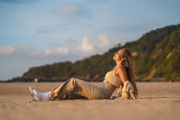 Foto de foco raso de uma jovem loira branca durante o pôr do sol na praia perto do mar