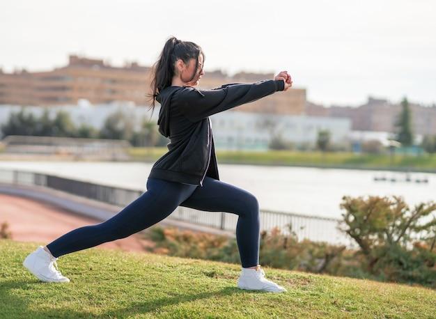 Foto de foco raso de uma jovem mulher branca durante seu treino no parque