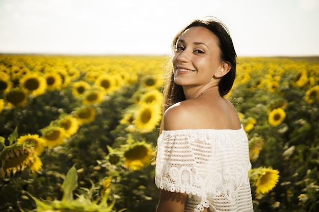 Foto de foco raso de uma linda mulher branca em um campo de girassóis ao nascer do sol