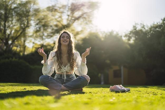 Foto de foco raso de uma linda mulher caucasiana espanhola com cabelo encaracolado, meditando