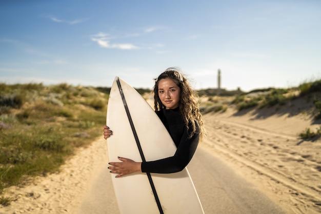 Foto de foco raso de uma mulher atraente abraçando uma prancha de surfe no meio de uma estrada na espanha