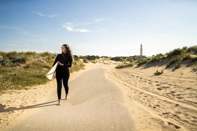 Foto de foco raso de uma mulher atraente carregando uma prancha de surfe