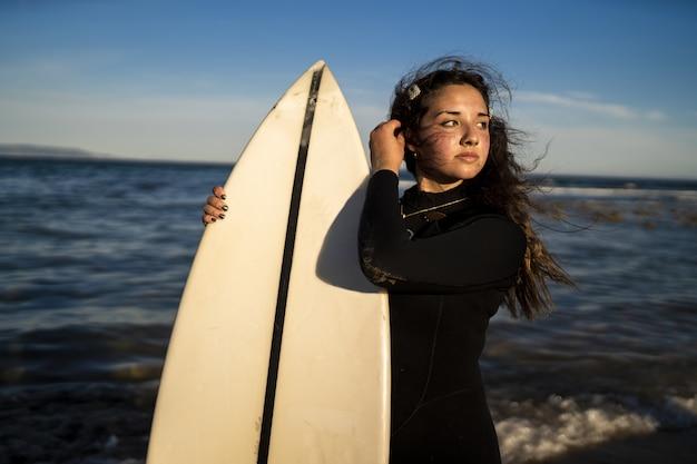 Foto de foco raso de uma mulher atraente posando à beira-mar na espanha, segurando uma prancha de surfe