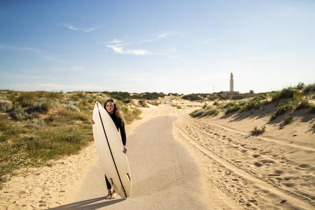 Foto de foco raso de uma mulher atraente segurando uma prancha de surfe no meio de uma estrada na espanha