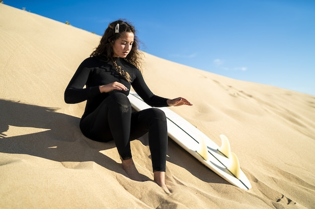 Foto de foco raso de uma mulher atraente sentada em uma colina arenosa com uma prancha de surfe ao lado