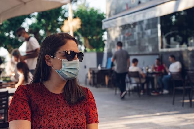 Foto de foco raso de uma mulher branca usando uma máscara médica e óculos escuros sentada em um café