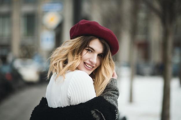 Foto de foco raso de uma mulher loira atraente feliz em roupas de inverno quente posando na rua