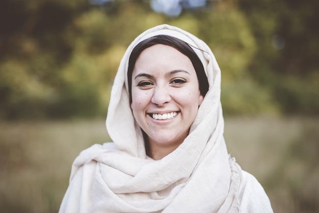 Foto de foco raso de uma mulher vestindo uma túnica bíblica e sorrindo para a câmera