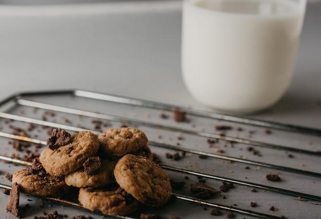 Foto de foco seletivo da grelha de cozimento com deliciosos biscoitos de chocolate redondos e um copo de leite