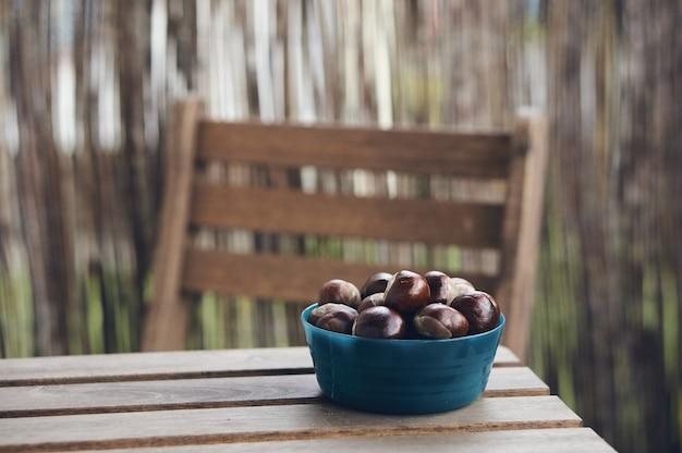 Foto de foco seletivo de castanhas em uma tigela azul sobre uma mesa de madeira