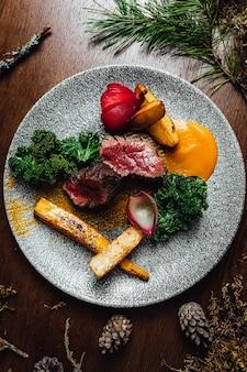 Foto de foco seletivo de deliciosa carne cozida com vegetais