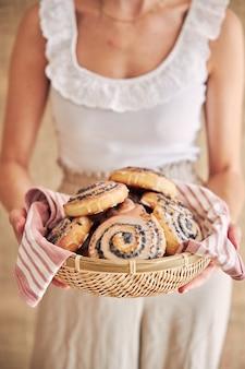 Foto de foco seletivo de deliciosos rolos de semente de papoula com cobertura de açúcar em uma cesta