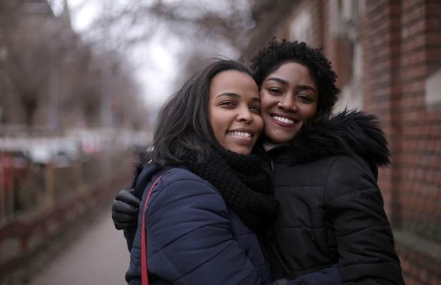 Foto de foco seletivo de duas amigas abraçadas na rua