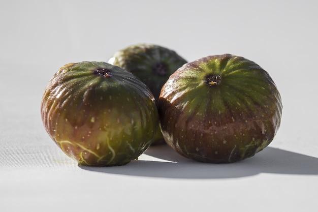 Foto de foco seletivo de figos isolados na mesa branca