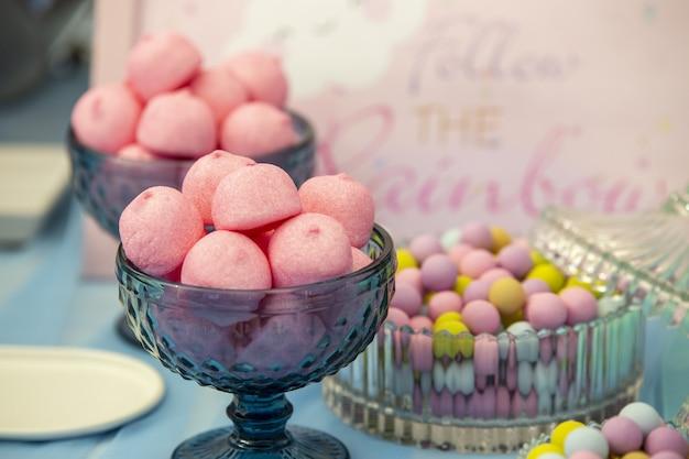 Foto de foco seletivo de marshmallows rosa em uma tigela de vidro