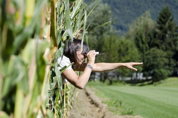 Foto de foco seletivo de mulher olhando através de binóculos de uma janela
