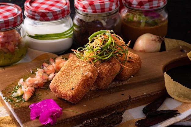 Foto de foco seletivo de nuggets de frango com salada na tábua de madeira