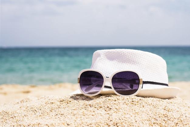Foto de foco seletivo de óculos escuros e um chapéu branco em uma praia arenosa