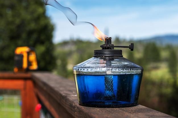 Foto de foco seletivo de óleo queimando em um recipiente colocado em uma superfície e árvores à distância