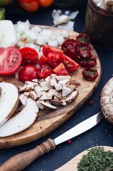 Foto de foco seletivo de tomates frescos e cogumelos fatiados com um fundo desfocado