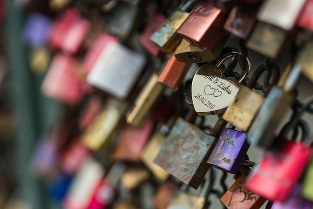 Foto de foco seletivo de um cadeado de amor em uma cerca