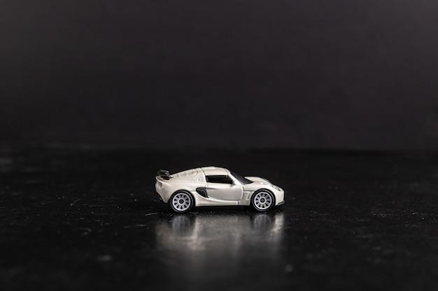 Foto de foco seletivo de um carro esporte de brinquedo branco em uma superfície preta