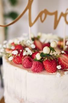 Foto de foco seletivo de um delicioso bolo de casamento branco com frutas vermelhas, flores e cobertura de bolo
