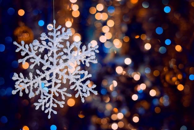 Foto de foco seletivo de um floco de neve decorativo em fundo desfocado bokeh