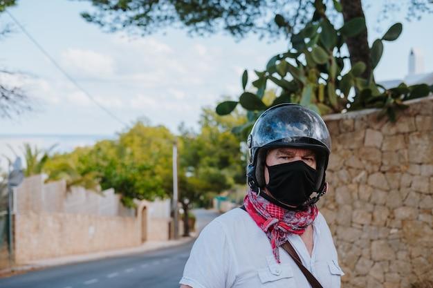 Foto de foco seletivo de um homem com uma máscara médica preta e um capacete de motociclista