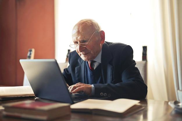 Foto de foco seletivo de um homem idoso, caucasiano, trabalhando em um laptop