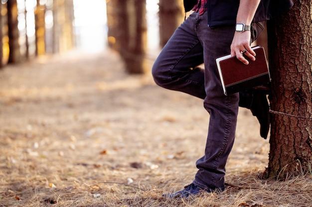 Foto de foco seletivo de um homem segurando um livro, posando em uma floresta