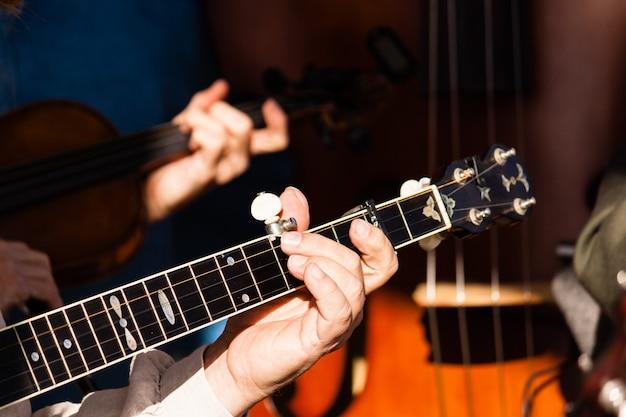 Foto de foco seletivo de um homem tocando violão
