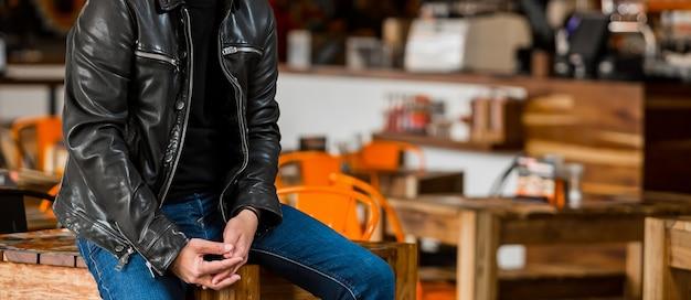 Foto de foco seletivo de um homem vestindo uma camisa preta, jaqueta de couro e jeans sentado em uma mesa