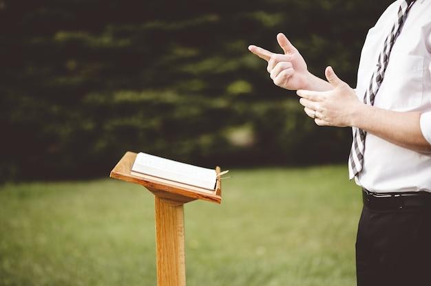 Foto de foco seletivo de um jovem em frente a uma igreja de madeira