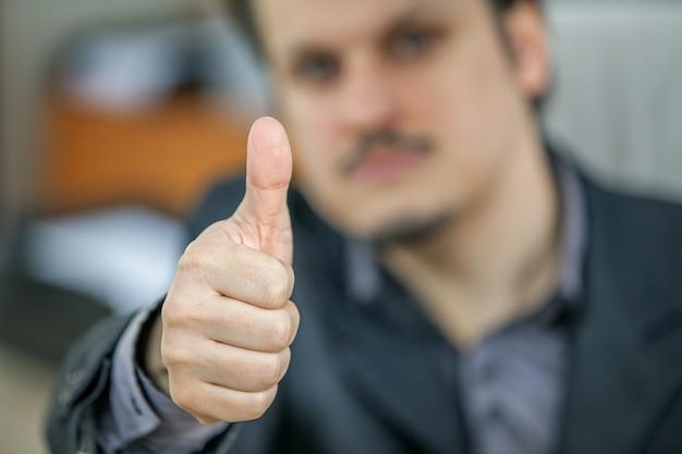 Foto de foco seletivo de um jovem empresário mostrando o polegar para cima